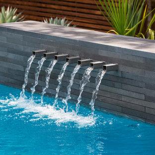 Esempio di una piscina minimalista rettangolare di medie dimensioni e dietro casa con fontane e pedane