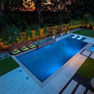 Imagen de piscina con fuente moderna, de tamaño medio, rectangular, en patio trasero, con entablado