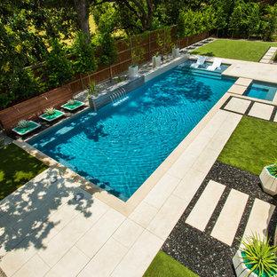 Diseño de piscina con fuente moderna, de tamaño medio, rectangular, en patio trasero, con entablado