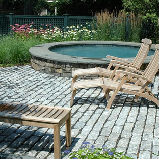 Country pool in Boston with a hot tub and brick pavers.