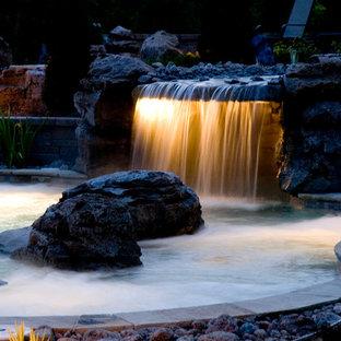 Ejemplo de piscina con fuente natural, asiática, grande, a medida, en patio trasero, con adoquines de hormigón