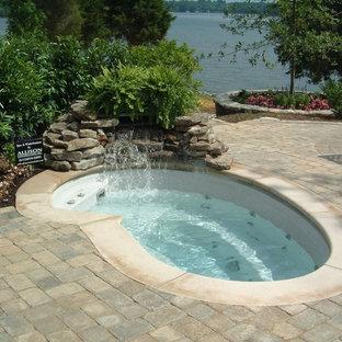 Modelo de piscinas y jacuzzis exóticos, de tamaño medio, tipo riñón, en patio trasero, con adoquines de ladrillo