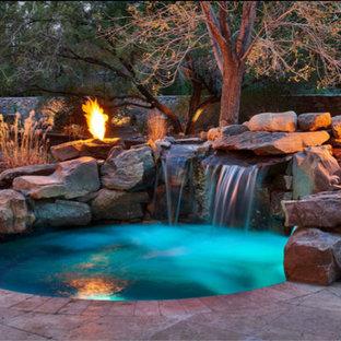 Immagine di una piscina classica rotonda di medie dimensioni e dietro casa con una vasca idromassaggio e pavimentazioni in pietra naturale