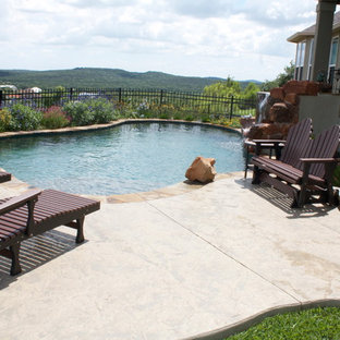 Hot tub - mid-sized rustic backyard stamped concrete and custom-shaped natural hot tub idea in Austin