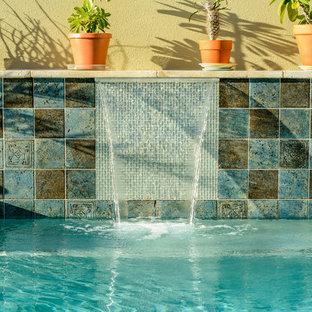 Esempio di una grande piscina monocorsia design rettangolare dietro casa con una vasca idromassaggio
