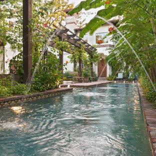Ejemplo de piscina con fuente alargada, mediterránea, grande, rectangular, en patio lateral, con adoquines de ladrillo