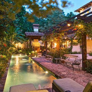 Foto de piscina con fuente alargada, mediterránea, grande, rectangular, en patio lateral, con adoquines de ladrillo