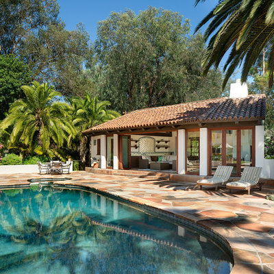 Example of a southwest backyard stone and round natural pool house design in San Diego