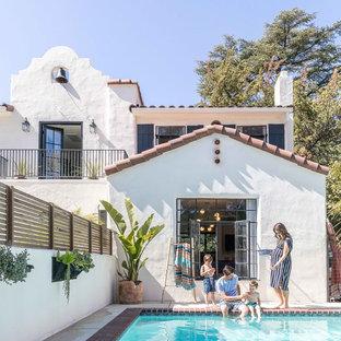 Imagen de piscina alargada, mediterránea, rectangular, en patio trasero, con losas de hormigón