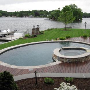Foto di una grande piscina naturale american style rotonda dietro casa con una vasca idromassaggio e pedane