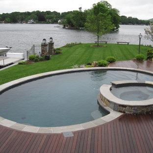 Imagen de piscina de estilo americano, grande, redondeada, en patio trasero