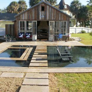 Idées déco pour un grand couloir de nage arrière industriel rectangle avec un bain bouillonnant et des pavés en béton.