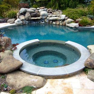Exempel på en mellanstor amerikansk rund gårdsplan med pool, med spabad och naturstensplattor