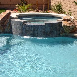 Foto de piscinas y jacuzzis naturales, tropicales, pequeños, redondeados, en patio trasero, con entablado