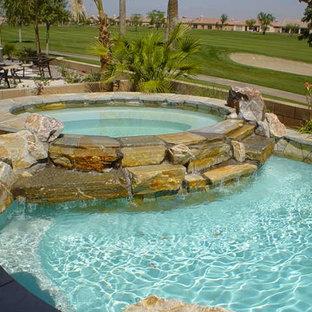 Esempio di una piccola piscina naturale tropicale rotonda con una vasca idromassaggio e pedane