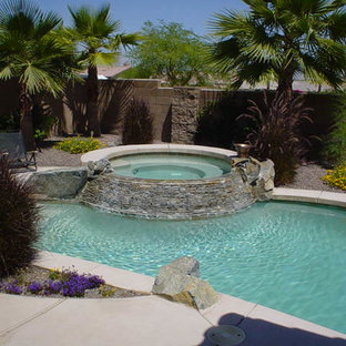 This is an example of a small tropical round natural pool in Los Angeles with a hot tub and decking.