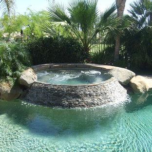 Immagine di una piccola piscina naturale tropicale rotonda dietro casa con una vasca idromassaggio e pedane