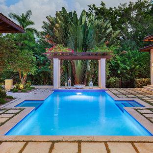 Diseño de piscina alargada, exótica, de tamaño medio, rectangular, en patio trasero, con adoquines de hormigón