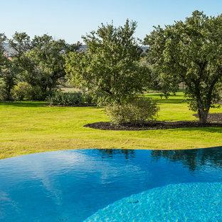 Foto di un'ampia piscina a sfioro infinito chic personalizzata dietro casa con pavimentazioni in pietra naturale