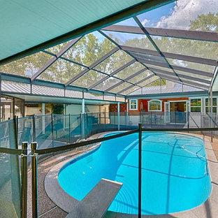 Ejemplo de casa de la piscina y piscina clásica, de tamaño medio, tipo riñón y interior, con granito descompuesto