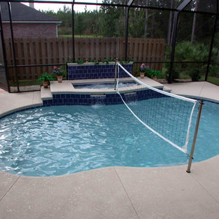 Inspiration for a mid-sized traditional backyard kidney-shaped lap pool in Jacksonville with a hot tub and concrete slab.