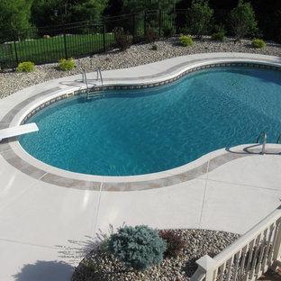 Ejemplo de piscina tradicional, de tamaño medio, a medida, en patio trasero, con suelo de hormigón estampado