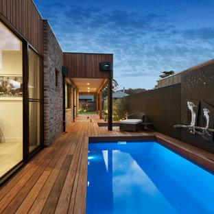 Ispirazione per una grande piscina naturale minimalista rettangolare nel cortile laterale con paesaggistica bordo piscina e pedane