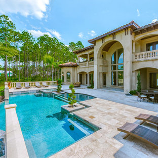 Photo of a mediterranean back custom shaped swimming pool in Jacksonville with a water feature.