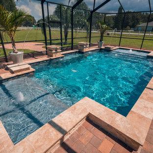 Ejemplo de piscina natural, contemporánea, de tamaño medio, rectangular, en patio trasero, con adoquines de ladrillo
