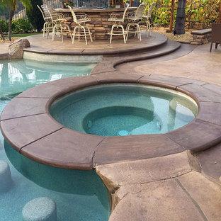 Imagen de piscinas y jacuzzis exóticos, grandes, a medida, en patio trasero, con suelo de hormigón estampado