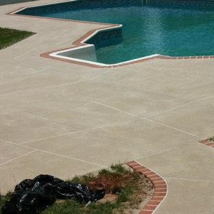 Imagen de casa de la piscina y piscina alargada, clásica, grande, tipo riñón, en patio trasero, con suelo de hormigón estampado