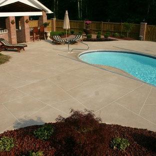 Diseño de casa de la piscina y piscina alargada, tradicional, grande, tipo riñón, en patio trasero, con suelo de hormigón estampado
