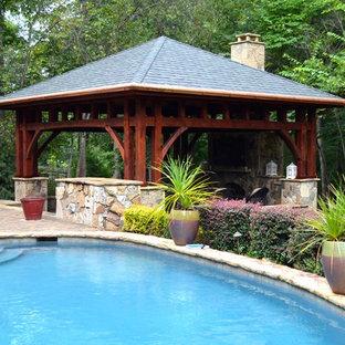 Modelo de piscina grande, a medida, en patio trasero, con adoquines de ladrillo