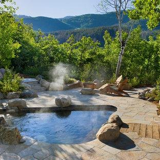 Стильный дизайн: бассейн произвольной формы на заднем дворе в стиле рустика с покрытием из каменной брусчатки и джакузи - последний тренд