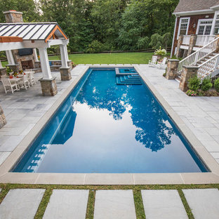 Elegant backyard concrete paver and rectangular pool house photo in New York