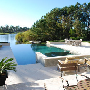 Example of a classic backyard tile and rectangular infinity pool design in Other