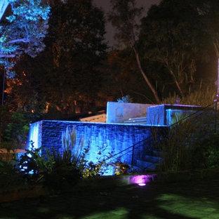 Idee per una grande piscina monocorsia contemporanea rettangolare dietro casa con una vasca idromassaggio e pavimentazioni in pietra naturale