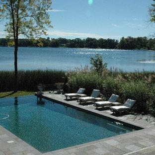 Diseño de piscinas y jacuzzis infinitos, clásicos renovados, grandes, rectangulares, en patio trasero, con adoquines de piedra natural