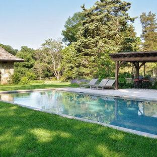Foto di una grande piscina monocorsia stile americano rettangolare dietro casa con fontane e pavimentazioni in cemento