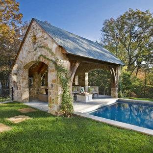 Foto di una grande piscina monocorsia chic rettangolare dietro casa con una dépendance a bordo piscina e pavimentazioni in pietra naturale