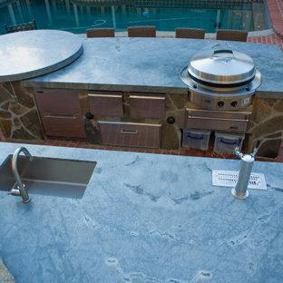 Foto de piscina natural, clásica, extra grande, a medida, en patio trasero, con adoquines de ladrillo