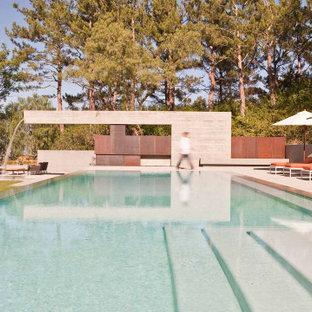 Ejemplo de piscina infinita, moderna, grande, rectangular, en patio trasero, con losas de hormigón