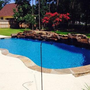 Imagen de piscina con fuente alargada, de estilo americano, de tamaño medio, tipo riñón, en patio trasero, con losas de hormigón