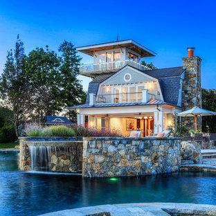 Foto de piscina con fuente costera, grande, a medida, en patio trasero, con adoquines de piedra natural