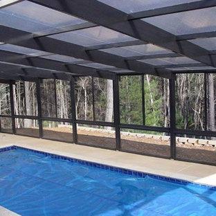Foto de piscina alargada, clásica, grande, rectangular y interior, con losas de hormigón