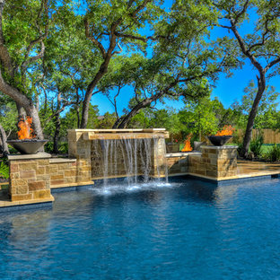 This is an example of a large mediterranean backyard custom-shaped pool in Austin with a hot tub and concrete pavers.