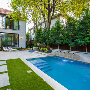 This is an example of a large mediterranean backyard rectangular lap pool in Dallas with a water feature and natural stone pavers.
