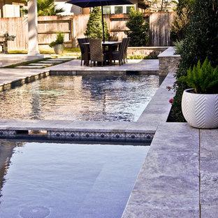 Ispirazione per una piccola piscina moderna personalizzata dietro casa con una vasca idromassaggio e pavimentazioni in pietra naturale