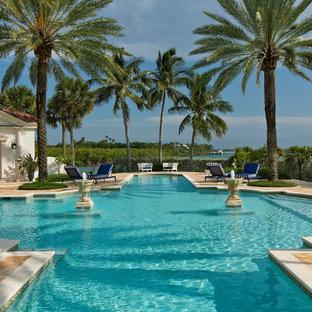 Idee per un'ampia piscina monocorsia mediterranea personalizzata dietro casa con pavimentazioni in pietra naturale