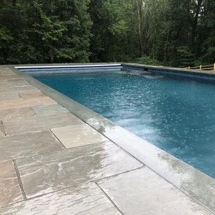 Imagen de piscina natural, actual, rectangular, en patio trasero, con adoquines de piedra natural